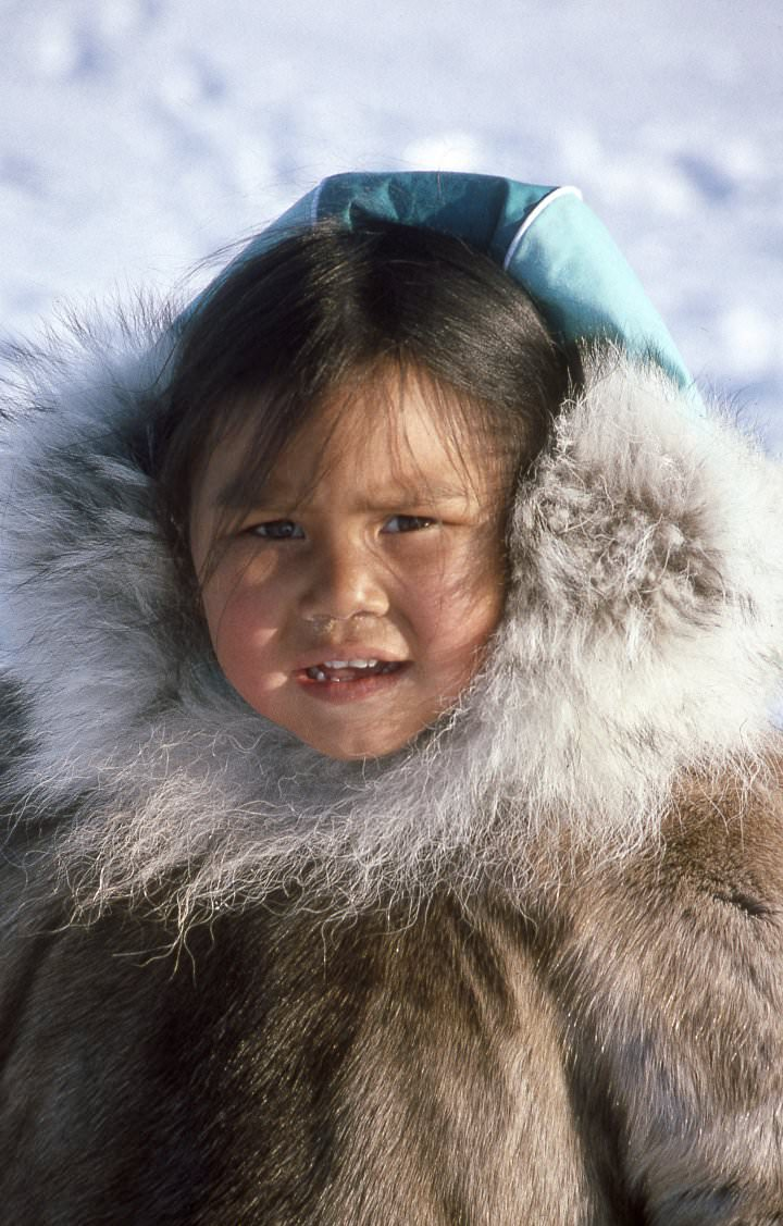 Inuit children are still dressed in caribou skin with hoods trimmed with wolf fur to keep the wind from their cheeks