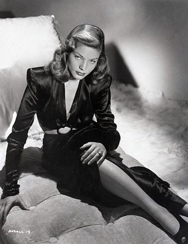 Full-length publicity portrait of actress Lauren Bacall. She is shown seated on a chaise lounge. Photo, 1945.