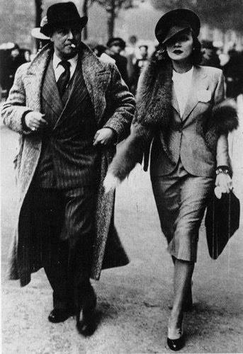 Marlene Dietrich adorned with a silver fox stole walking alongside her husband, Rudolf Sieber, 1930s.