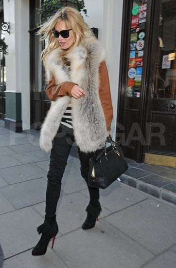 Kate Moss with a fox vest and black jeans