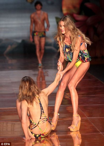 Model Ana Claudia Michels (L) falls and is being helped by another model during the runway of Blue Man creations