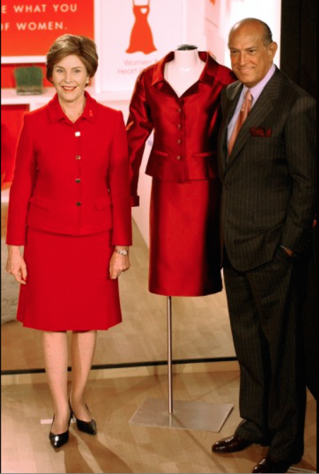 Laura Bush and Oscar de la Renta pose for photographers with an outfit she is donating to the Heart Truth 2004 collection in New York. The outfit was designed by de la Renta, Feb. 9, 2004