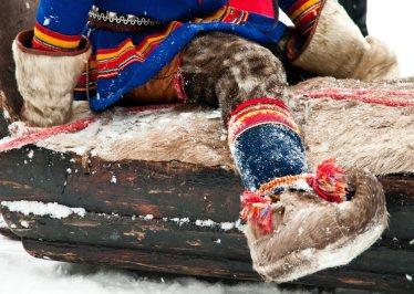 Boy dressed up in traditonal White reindeer fur for Jokkmokk's winter fair, Finland.
