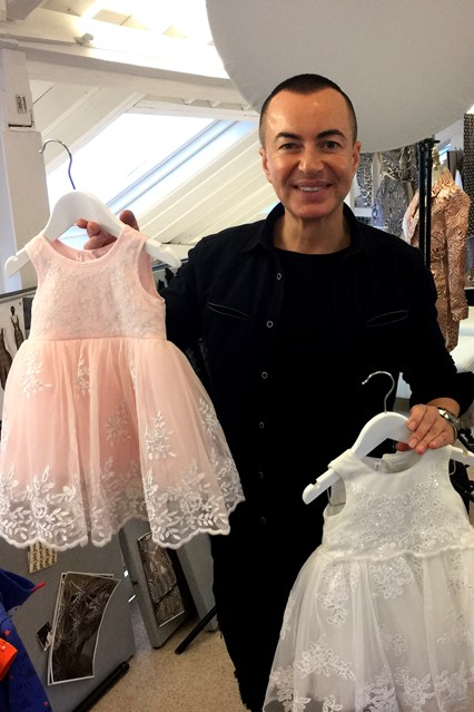 Designer Julien Macdonald holding up pieces from his children's 2016 collection at his London atelier