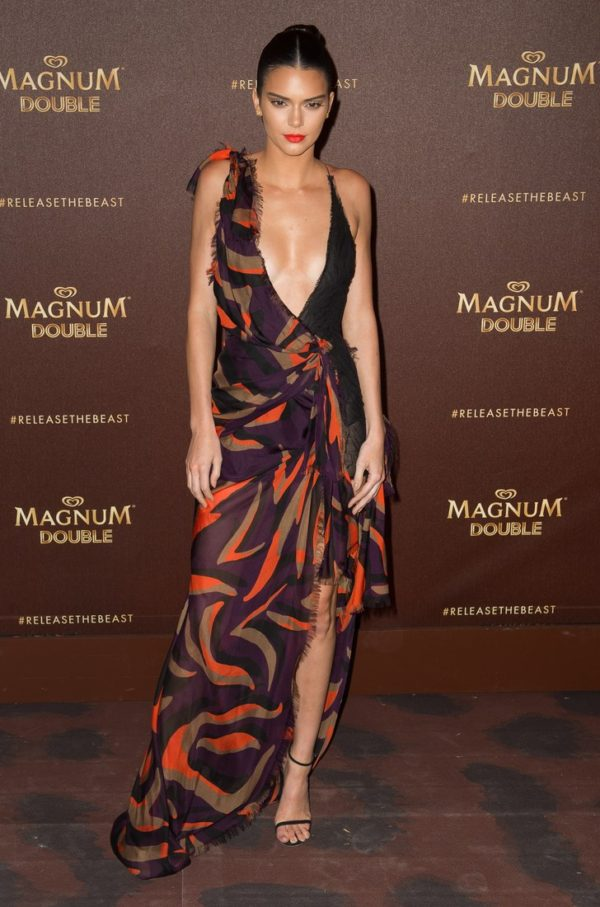 Kendall Jenner owned the red carpet down at the Magnum Beach Party in a printed orange and purple silk plunging gown by Versace that was so hot it would make anyone melt