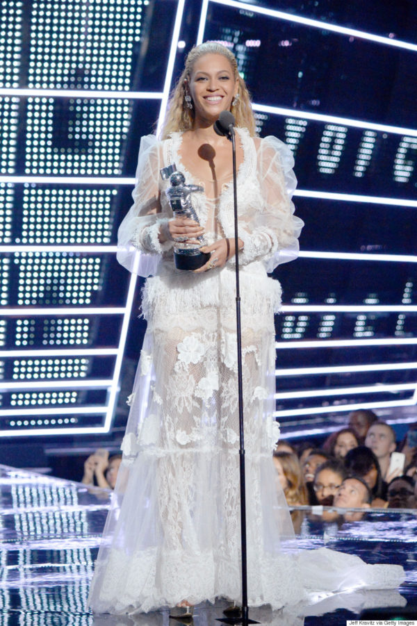"Beyonce accepts her award for Video of the Year for ""Formation"" in a white lace and sheer ????? gown. Oh, did we mention that she slayed the competition in more ways than one. 6 different outfit changes. Now that's commitment!"