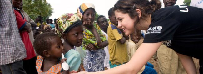 UNICEF Ambassador Selena Gomez reaches out to a young child while in Ghana