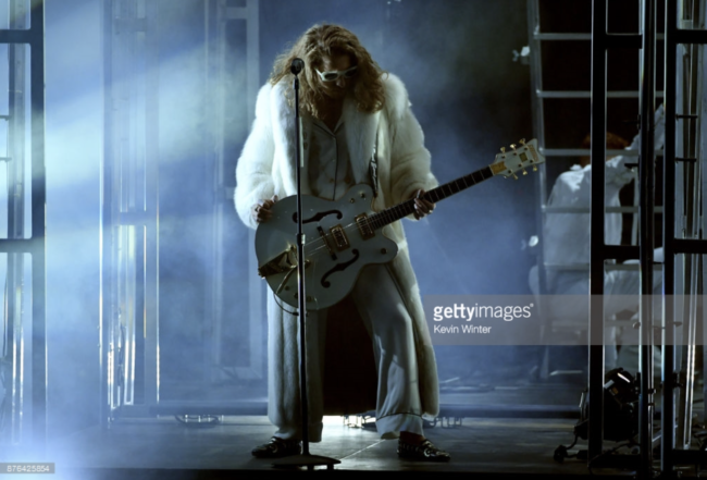 Watt more could you ask for in a rockstar. Musician Watt rocked the stage in his performance with Hailee Steinfeld in a spectacular white full length fox coat at the 2017 American Music Awards