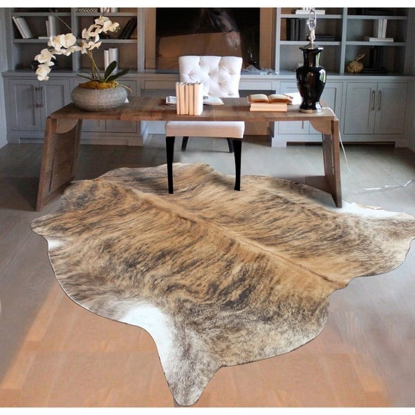 A natural cowhide rug perfectly placed add visual interest on hard surface floors home decor trends